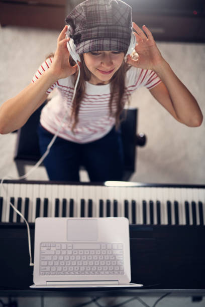 Teenager girl composing on digital piano Teenage girl composing on digital piano using modern ultrabook laptop. Nikon D8 keyboard player stock pictures, royalty-free photos & images