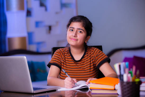 teenager girl doing her homework stock photo - girl study home laptop front imagens e fotografias de stock