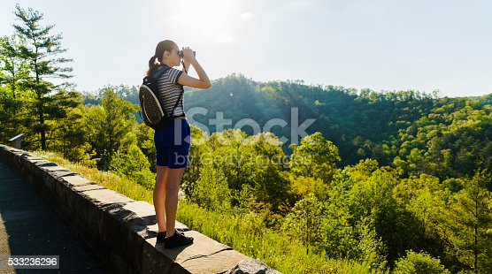 Teenager girl with binocular explore scenic view to Great Smoky Mountains and Cherokee National Forest from the Turkey Creek Overlook at Cherohala Skyway, Tennessee, North America, USA. Elevation 2630Ft.