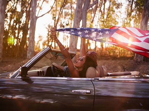 Teenager girl holding an American flag on a road trip Teenager girl holding an American flag during a road trip on a vintage convertible car while her boyfriend is driving with afternoon sun flare american flag tattoos for men stock pictures, royalty-free photos & images