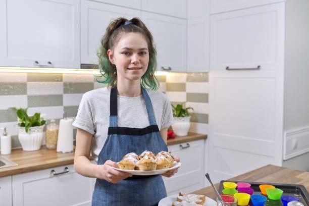Taze pişmiş muffins ile bir önlük genç kız stok fotoğrafı