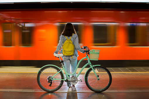 Teenager girl in jeans with bike standing on metro station