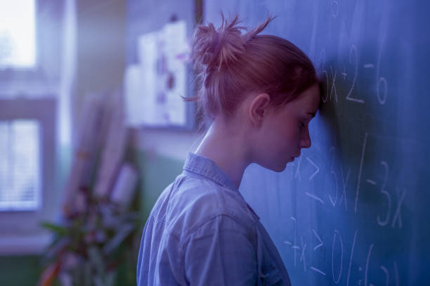 Teenager girl in math class overwhelmed by the math formula. Pressure, Education, Success concept. stock photo
