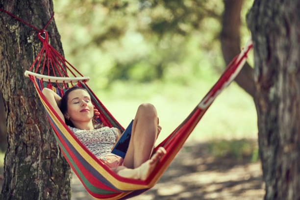 teenager girl lay in hammock with book and kitten outdoor summer garden photo stock photo