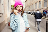 Teenager girl listening music with headphones from a smart phone in the street of Paris, France