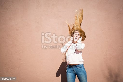 istock Teenager girl listening to the music and dancing 825039174