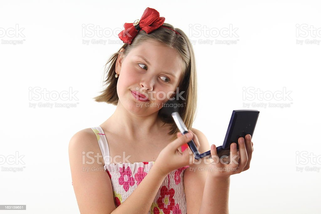 Teenager girl looks at mirror doing makeup royalty-free stock photo