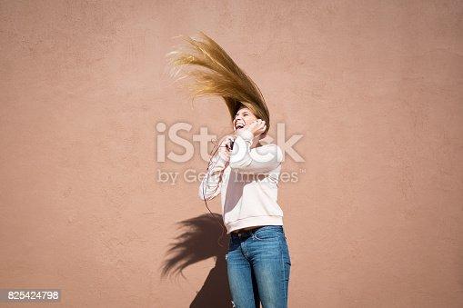 istock Teenager girl loving her music selection 825424798