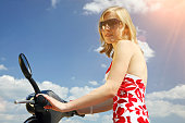 beautiful blond girl on a scooter with nice sky