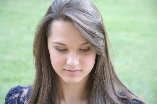 young and beautiful teenage girl lean body model long brown hair and light makeup posing for fashion shoot in the park closeup sad expression