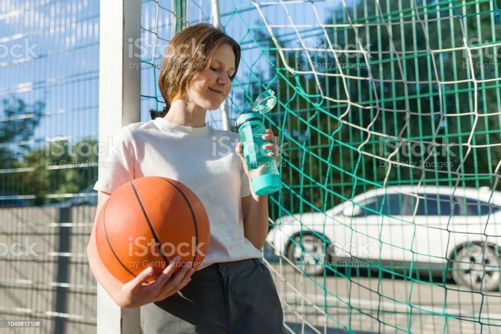 Teenager girl playing basketball with ball on the basketball court...