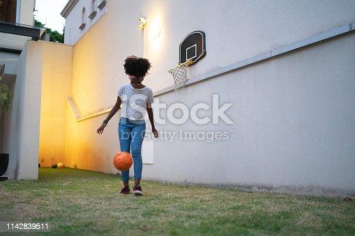 Teenager girl playing doing kick-ups in the backyard