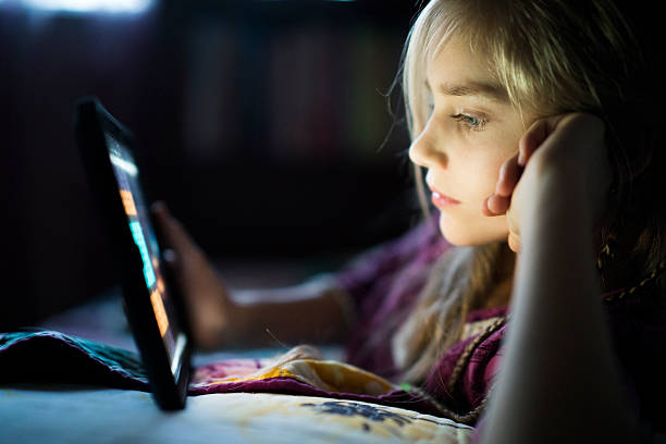 Teenager girl reading from tablet at night in the bed stock photo