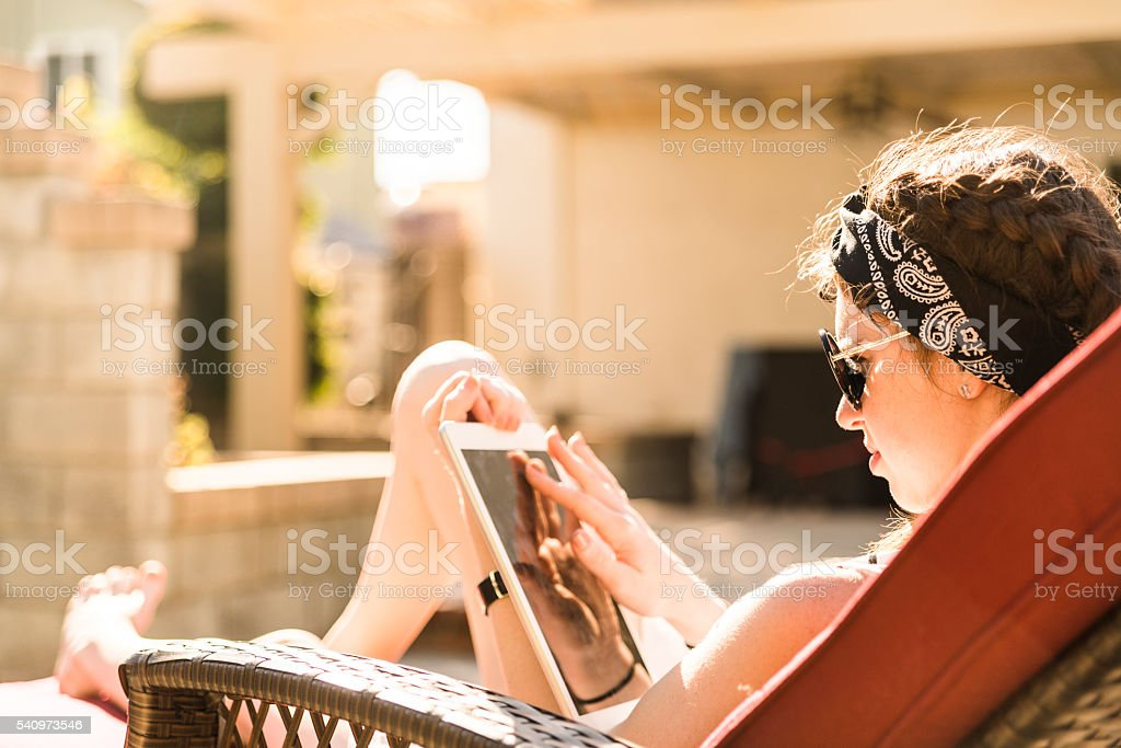 Teenager girl reading tablet while sitting in shezlong on backyard stock photo