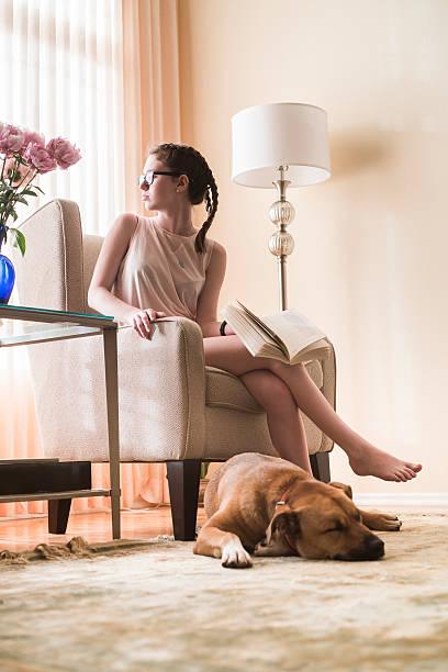 teenager-mädchen liest buch im wohnzimmer mit hund in der nähe - mädchen vorhänge stock-fotos und bilder