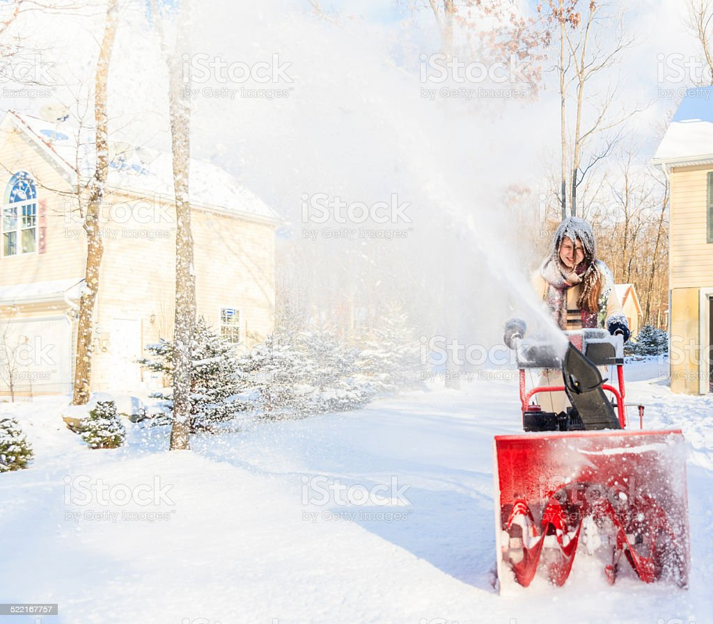Teenager girl remove the snow with snowplow stock photo