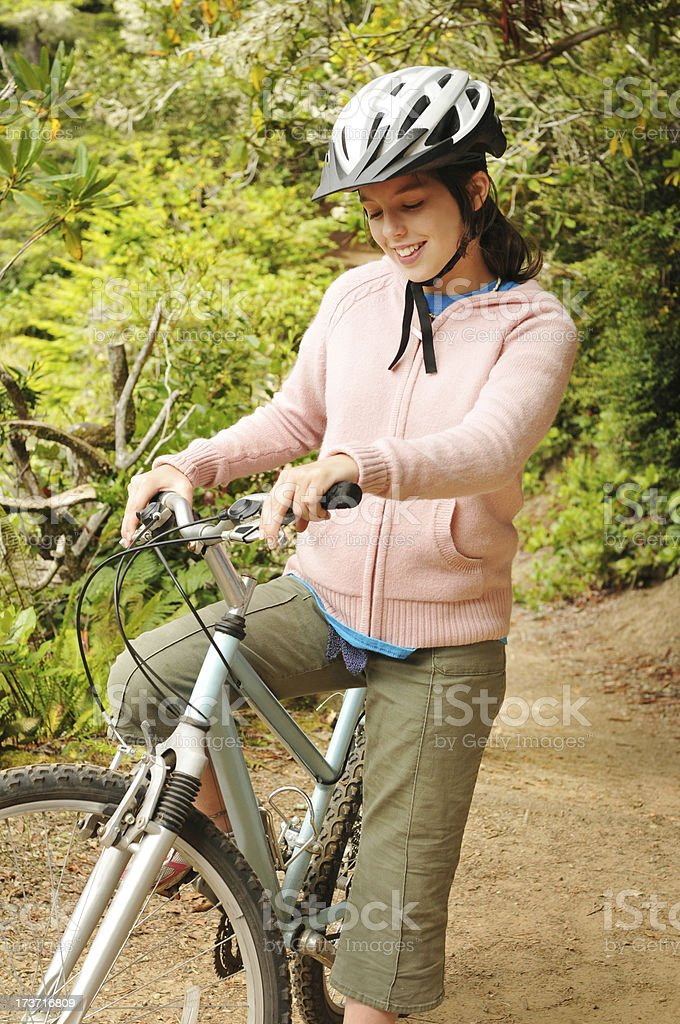 Teenager girl riding bicycle, wearing helmt on  woodsy trail royalty-free stock photo