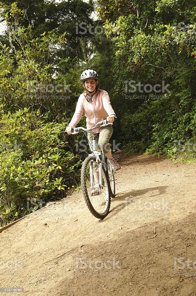Teenager girl riding bicycle, wearing helmt onwoodsy trail royalty-free stock photo