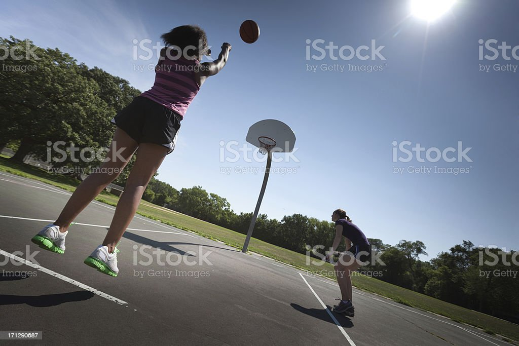 Teenager Girl Shooting Basket in Summer Outdoor Basketball Game stock photo