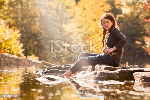 Teenager girl sits on the rock at the Tunkhannock Creek river, in the forest in Poconos, Pennsylvania