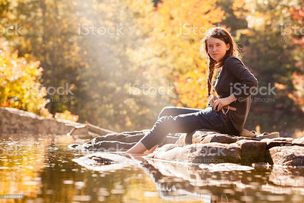 Teenager girl sits on the rock at the river stock photo