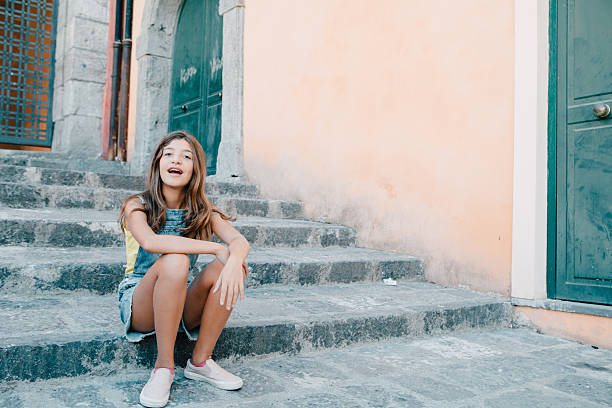 Teenager Girl Sitting on Stairs Outdoors stock photo
