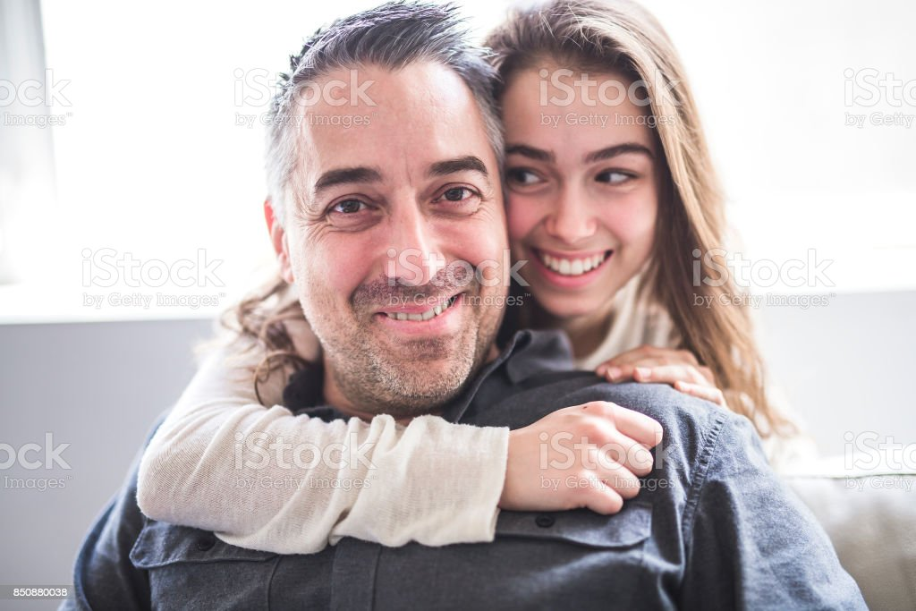 Teenager girl sitting on window with father stock photo