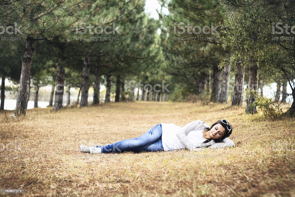 Teenager girl sleeping in the park at autumn royalty-free stock photo