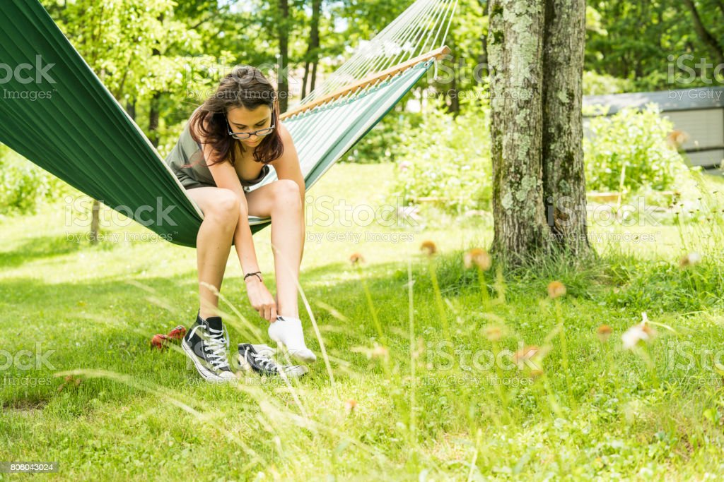 Teenager girl taking on shoes before leaving the hammock stock photo