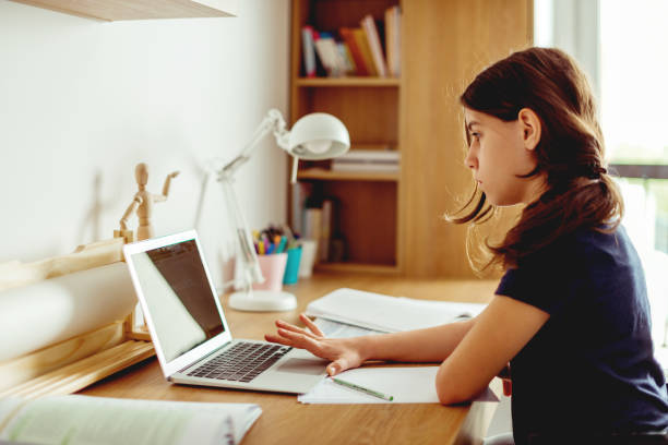 Teenager girl typing on laptop, in her room stock photo