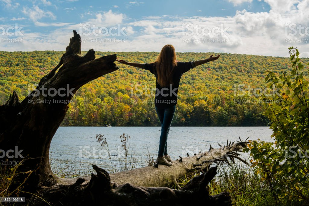 Teenager girl walking on the falled tree over the lake in Poconos stock photo