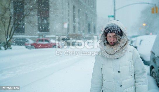 Teenager girl walks under snowfall at the street in Manhattan, New York City, NY, during the snowstorm Jonas