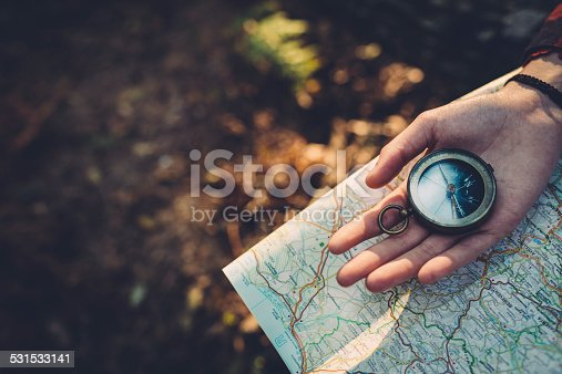 istock Teenager girl with Compass Reading a Map in the forest 531533141