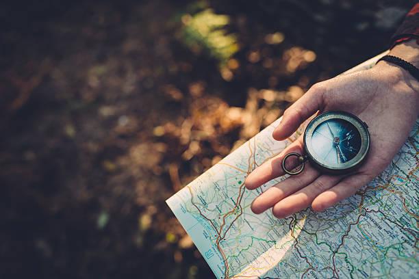 teenager-mädchen mit kompass lesen der karte im wald - karte navigationsinstrument stock-fotos und bilder