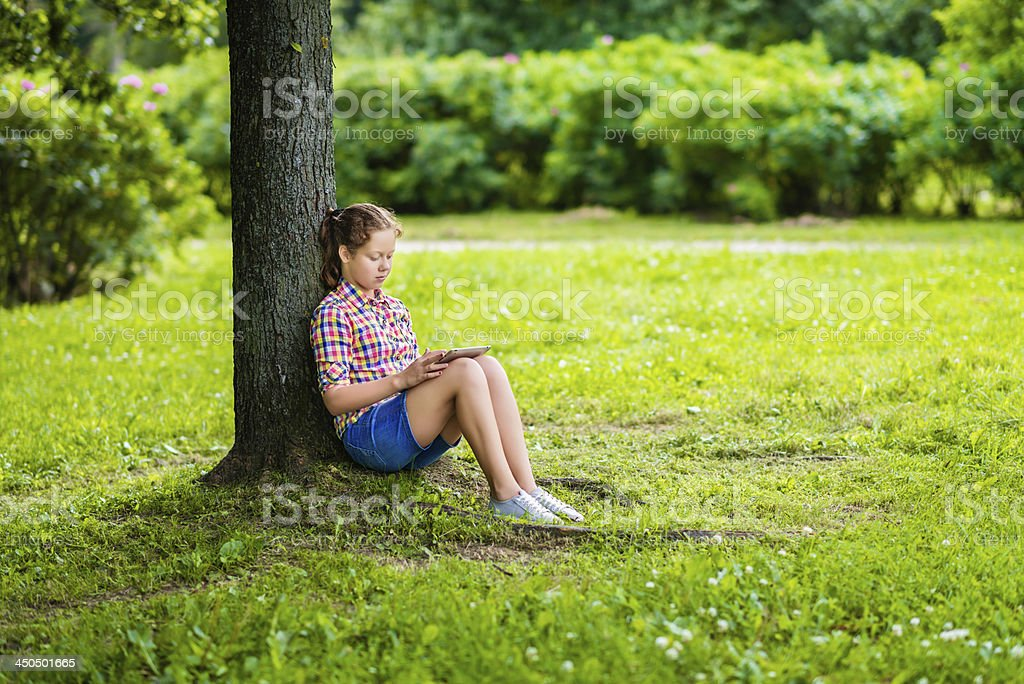 Teenager girl with digital tablet sitting in the park royalty-free stock photo