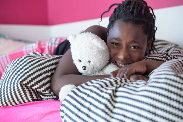 Teenager girl with teddy bear in pink cozy bedroom stock photo