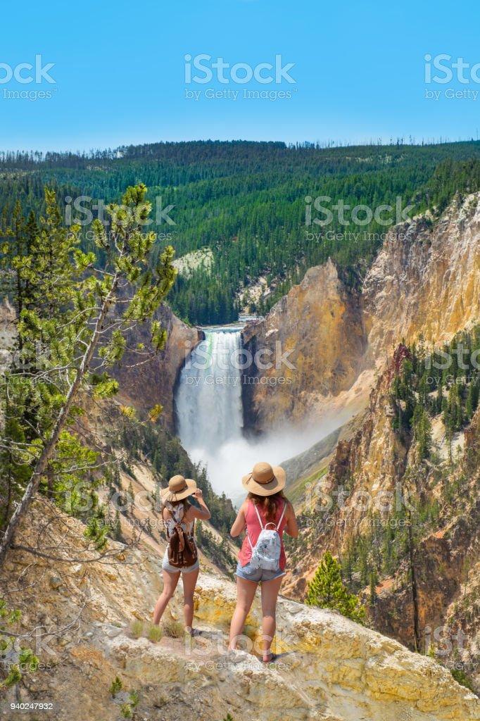 Teenager girls on summer vacation, looking at beautiful waterfall. stock photo