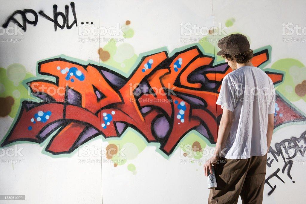 Teenager Graffiti Artist Spray Painting Wall Street Art, Rebelling, Vandalizing royalty-free stock photo