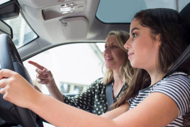 teenager mit treibende lektion mit weiblichen lehrer - autos für fahranfänger stock-fotos und bilder