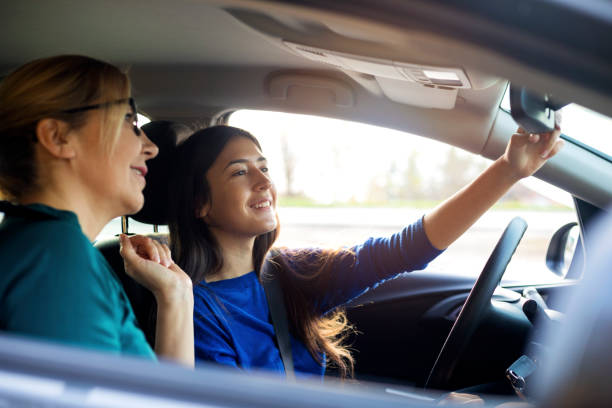 Teenager having driving lesson with female instructor A teenage girl sitting behind the steering wheel of a car and listening to her driving instructor as she drives. driving instructor stock pictures, royalty-free photos & images