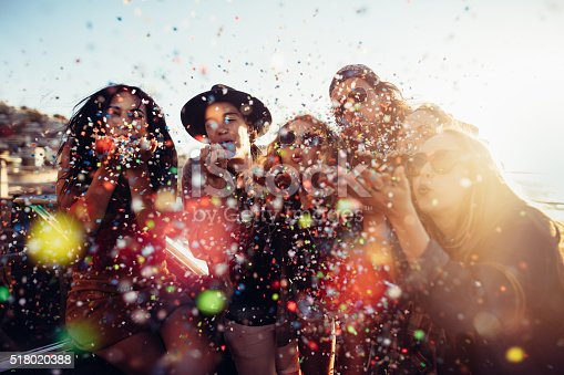 Group of teenager hipster friends celebrating by blowing colorful confetti from hands with sunset sun flare