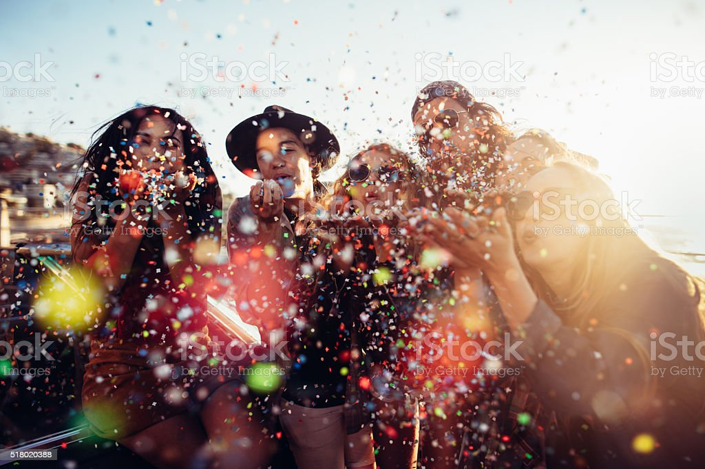 Teenager hipster friends celebrating by blowing colorful confetti from hands stock photo