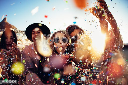 istock Teenager hipster friends partying by blowing colorful confetti from hands 513550806