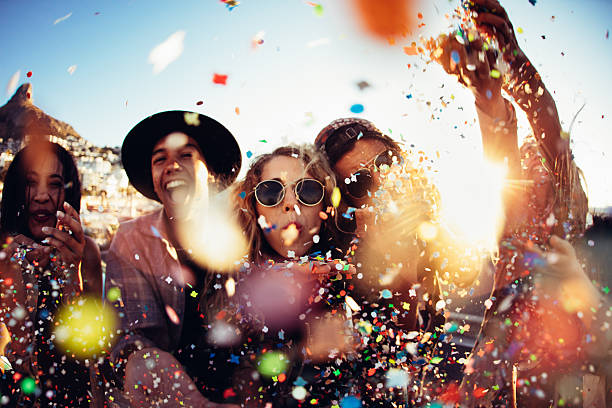Teenager hipster friends partying by blowing colorful confetti from hands Group of teenager hipster friends partying by blowing and throwing colorful confetti from hands with sunset sun flare celebration stock pictures, royalty-free photos & images