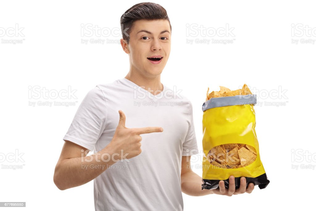 Teenager holding a bag of chips and pointing stock photo