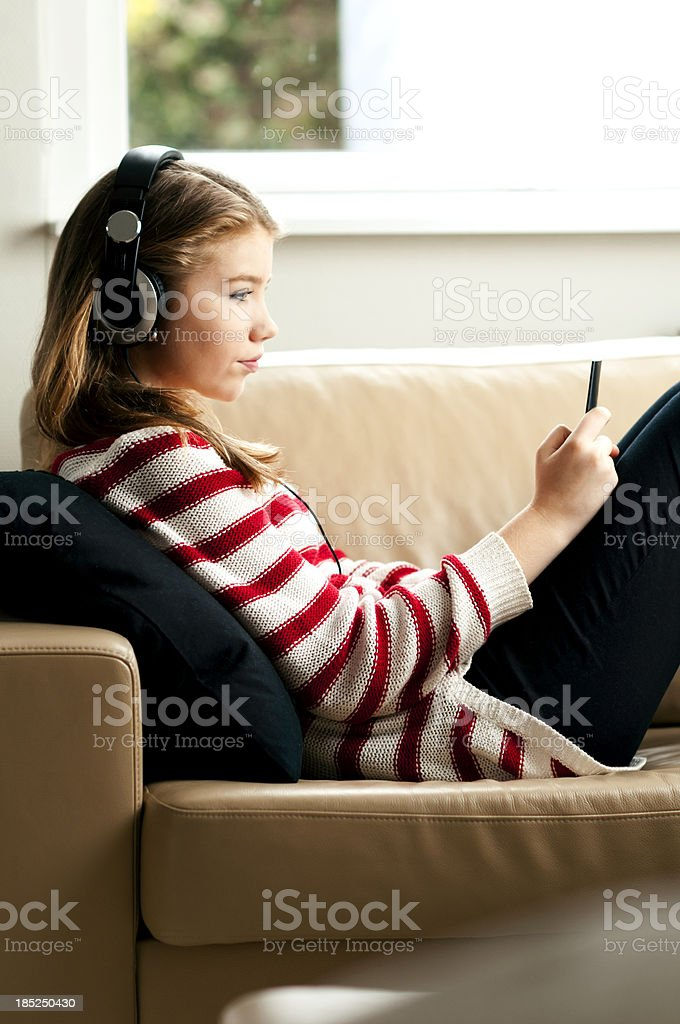 Teenager holds smartphone and listens to music royalty-free stock photo