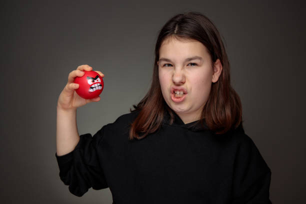 teenager imitating facial expression of red angry squeeze ball stock photo
