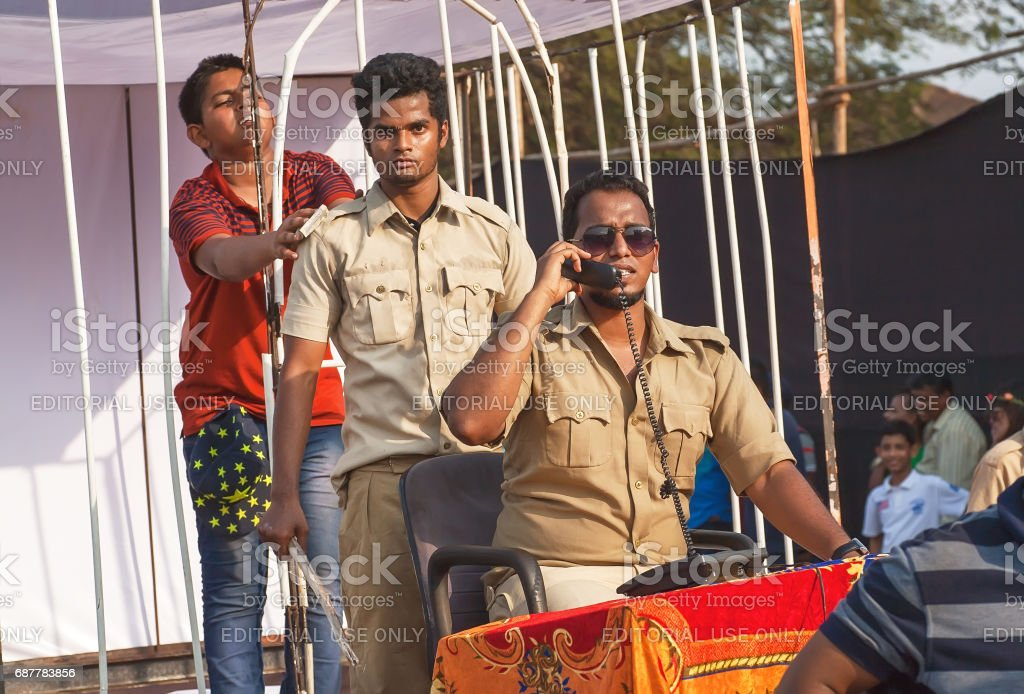 Teenager imprisoned in a cell by actors in uniform playing corruption police department at Goa carnival stock photo
