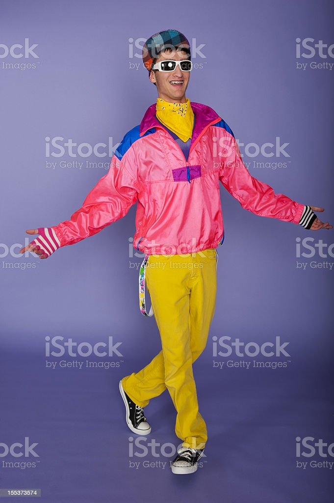 Teenager in 1980s fluorescent pink and yellow with cap stock photo