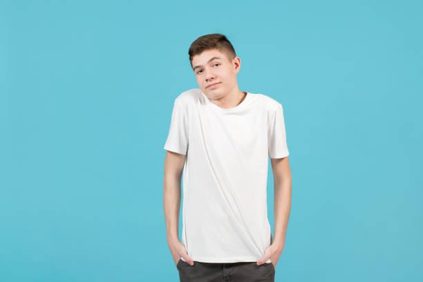 Un adolescente con una camiseta blanca sonríe inciertamente, se encoge de hombros - foto de stock